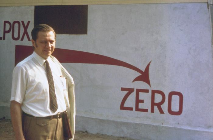 "This historic image, from 1974, depicted Dr. Donald A. Henderson, standing in front of a ""Smallpox Zero"" sign, which was outside the Bangladesh National Smallpox Eradication Program Center, located in the country's capital city of Dhaka. During the 1960s and 70s, Dr. Henderson headed the international effort to eradicate smallpox, and to achieve the ""Smallpox Zero"" status for all countries throughout the World, a goal which was successfully reached. Image/CDC"