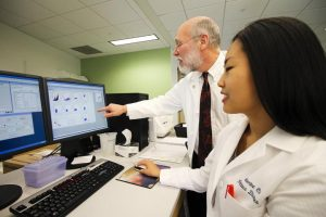 Daniel Hoft, M.D. Ph.D., director of SLU's division of infectious diseases, and Catherine Cai, a SLU MD/PhD candidate, review data that shows detailed information about characteristics of individual T cells at SLU's flow cytometry research core. CREDIT Saint Louis University
