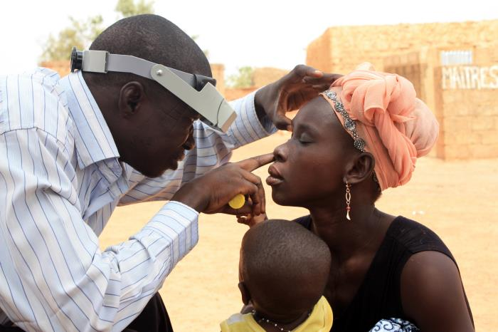 An outdoor examination of a woman's right eye, looking for symptoms of trachoma/CDC